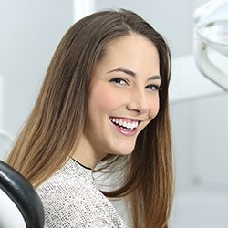 woman in grey shirt smiling bright