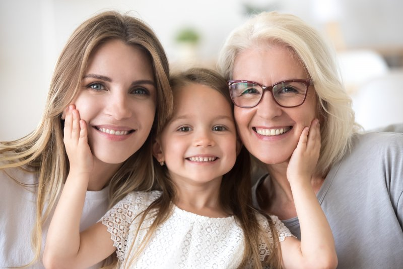 three generations of women with the grandmother smiling after undergoing full-mouth reconstruction