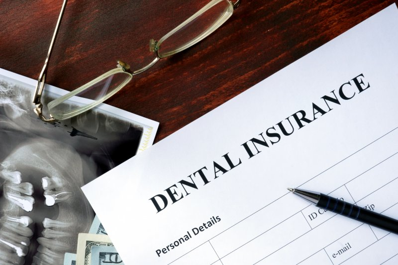 a table complete with a dental X-ray, glasses, a dental insurance form, and a pen